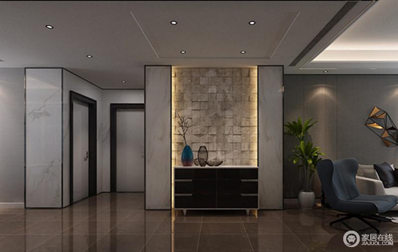 玄关区设计的十分简单,却呈现着独特的后现代感,充满了诗情雅性;金属框裱起白色板材,几何感的设计与方块感的墙面在灯光的掩映下颇为温情,黑色边柜上卷逸的艺术品点缀出文艺气质。