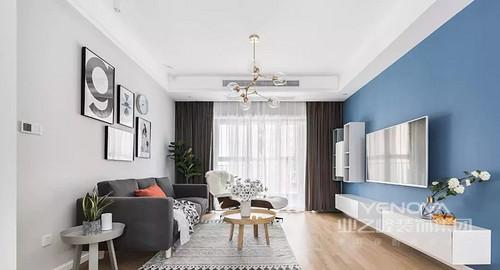 客厅地面通铺木色地板,墙面采用蓝灰两种色调,视觉上具有层次感。