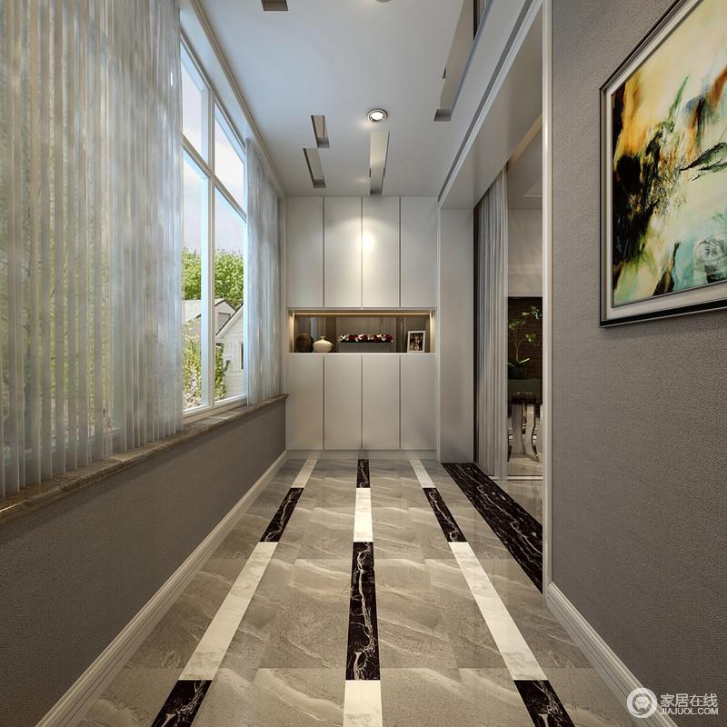 入户门走廊地面上,设计师用拼接材质的线条制造视觉上的延展,并与天花板上镜面形成呼应;线条的延续与入墙的玄关柜柜面线条汇聚,为空间注入趣味和格调;大面积的飘窗则带来充足光线,令入户区愈加显得轻盈悦动。