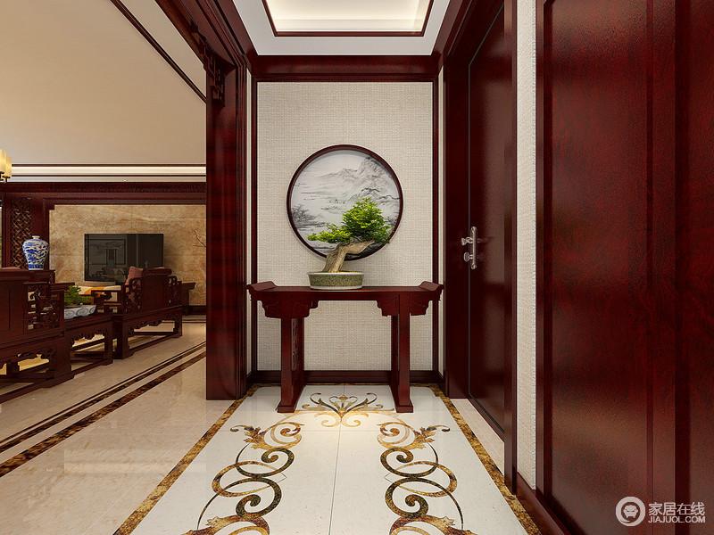 门厅地面上缱绻的拼花造型动人,使视觉延展至背景墙处;传统中式翘边案几上,盆栽绿植与背景墙圆形画框,相互渲染营造,描绘出的远山田园的闲逸静趣;配上温润的红木门框,空间满溢出平和自然的惬意。