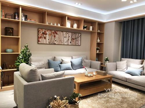 客厅沙发墙定制的环绕型格子架,不仅作为装饰背景,更大大增加存储空间;原木温和自然,呼应着方正的双层茶几;浅灰色布艺沙发柔和雅致,水蓝色靠包清新点缀,画作图案与绿植对比辉映,空间美观实用。