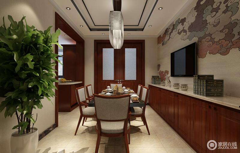 餐厅酒柜靠墙,以一字型地柜形式存储,呼应着厨房的拐角吧台,拼接的墙面上饰以优美的祥云,烘托出古典古韵;黑色的方形餐桌,搭配浅灰布艺棕红木餐桌,在绿植的点缀下,呈现出质朴而安逸的情调。