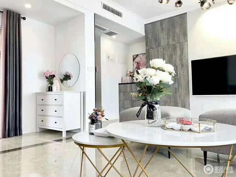 客厅线条简单,以灰色板材来构建空间层次,白色圆几搭配灰色沙发更是让空间多了素雅;转角处的白色收纳柜、圆镜将方圆感融入空间,让空间更为和谐。