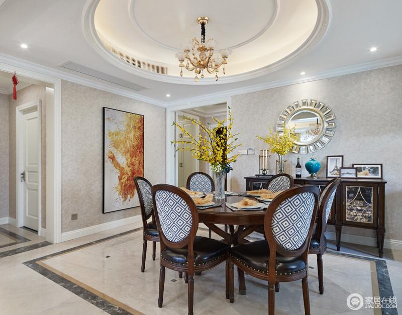 """餐厅的吊灯还融入了美式的元素,""""轻装修""""是为了更好的突出家居,餐厅的家居色彩保持了中式的深色实木风格,墙面选择的是米色系列的墙布,餐桌边墙上挂着大幅的画和镜子起到了点睛的作用。"""