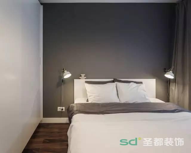卧室的背景墙是用灰色的墙纸,两侧是白色的墙和衣柜,现代风格的壁灯。