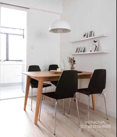 白色调的餐厅没有杂色,显得纯净了许多;墙面的收纳架以多样的简画增添文艺风,白色北欧吊灯与黑色餐椅以黑白组合尽显经典,实木桌与器物营造起生活的简朴之调。