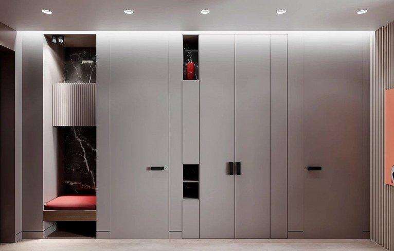 入口处巧妙的设置了一个内嵌式的座椅  为进出换鞋提供方便  一旁灰色的墙面包含两个卧室门  以及一个双开门柜子