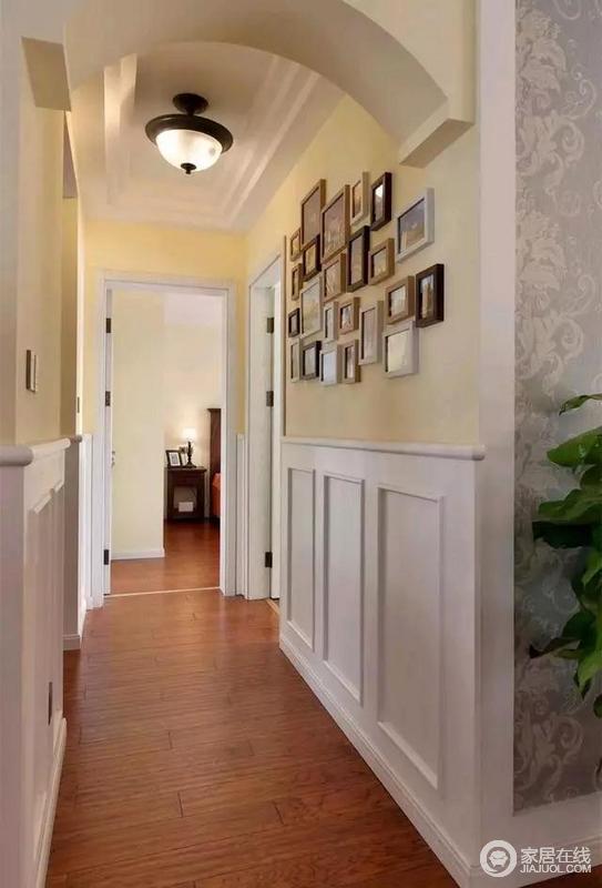 通往卧室的走道中间装了个拱门造型,墙脚也装了护墙板,右侧墙面上挂有一组温馨的照片。