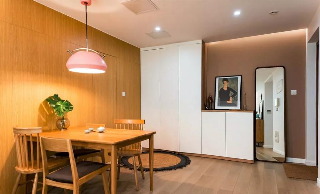 原本的卫生间门和入户门对着,卫生间隐形门的设计,消除了人心理上的尴尬。餐厅,粉红色的吊灯在一片原木的环境中有点跳跃,放在这里活跃气氛刚刚好。