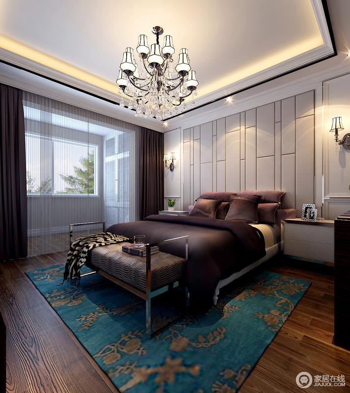 卧室主要以褐色木地板和咖色床品来中和乳白色的立面,延续空间的沉稳与低调;欧式华丽的吊灯散发出来的暖光,与蓝色地毯碰撞出复古;金属床尾凳上的皮革椅面颇为松软舒适,升华了空间的质感。