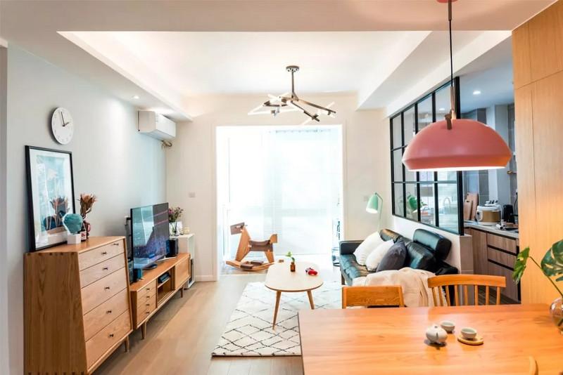 客厅,几何图形的地毯,原木的电视柜、五斗柜、小茶几和沙发都是典型的北欧风格。