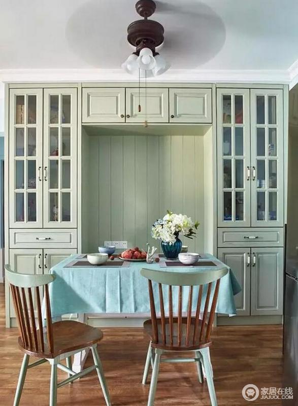 餐厅开放式的设计,与客厅形成互动,浅绿色橱柜具有收纳作用,与美式餐椅承接着田园清怡;蓝色桌布带着清新感,与餐盘和花器更显惬意。