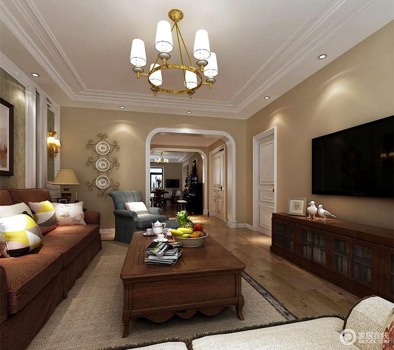 空间以驼黄色漆粉刷墙面,象牙白结构框裱出亮快,拱形结构和铁艺钟表让客厅多了一些形式之美;咖色美式沙发和蓝色扶手椅组成典雅,而编织藤条地毯和褐色实木家具浓郁着美式温馨。
