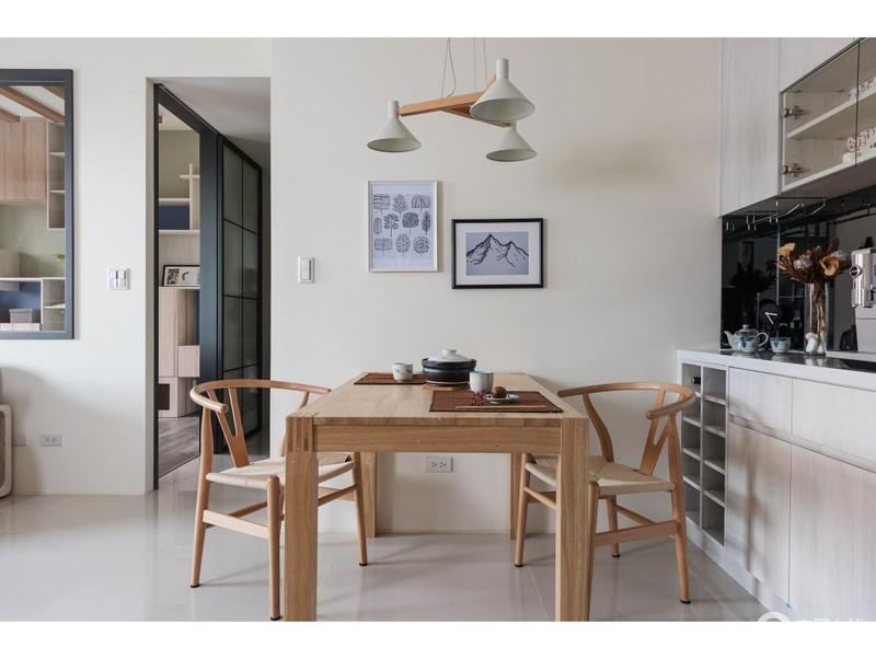 餐厅以米白色漆粉刷墙面,借挂画和吊灯让整个空间少了空洞;原木家具质地厚实,新中式太师椅又增添了文化气息,与白色橱柜解决了收纳问题。