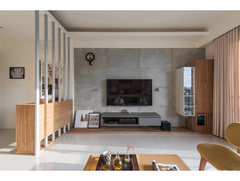 客厅的背景墙以灰色防水泥砖来铺贴,无形中让空间具有了工业气息;实木条的镂空给空间带来轻盈感,让空间轻薄了不少。