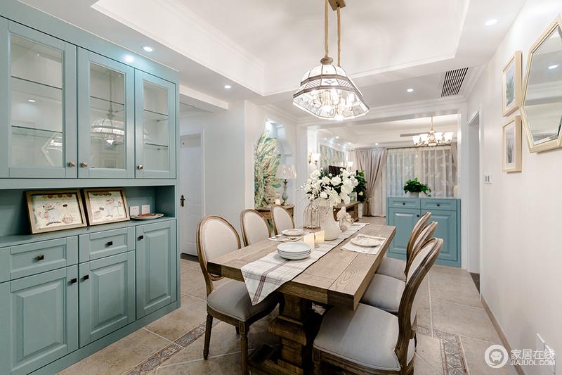 餐厅与客厅通过小吧台来区分,却不失空间的互动感;在白色调的基础上,搭配蓝色橱柜,令空间更为雅致;美式实木餐桌因为餐椅、桌巾和餐具的陈列极富品质;水晶灯的闪耀与花器的生机碰撞出空间的轻奢。