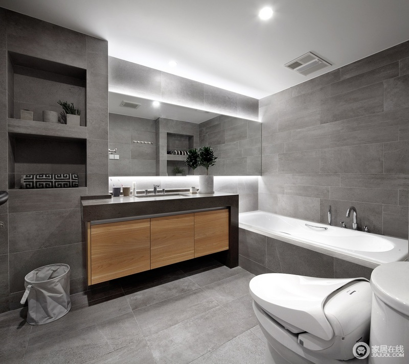 卫生间以深灰色砖石铺贴空间,冷调之中自带高贵与个性;墙体内隔出来的置物台与镜子的通透形成一种几何美学,而原木盥洗柜带来暖调,让你沐浴也是舒适的。