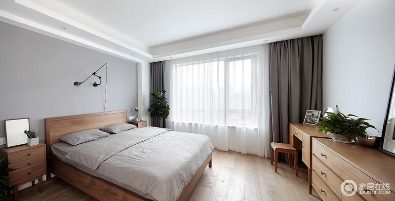 卧室以浅灰色漆粉刷墙面,实木家具的温实朴质给予空间一种暖调;而深灰色窗帘与浅灰色床品构成色彩对比,白色纱幔营造朦胧意境,渲染出一种轻盈感。