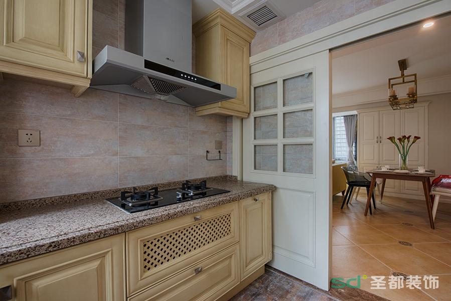 厨房和客厅采用了隔断式移门,厨房背景墙面以仿色方砖平铺,与米黄色的橱柜层次相碰撞。