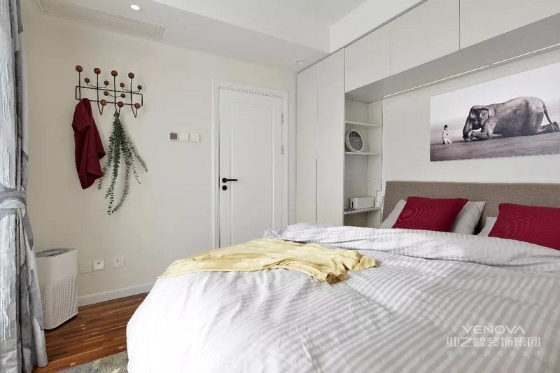 床头选用一体化的衣橱床柜,收纳格设计简单实用。卧室并没有太多装饰,选用简易衣架,挂衣帽也是很实用