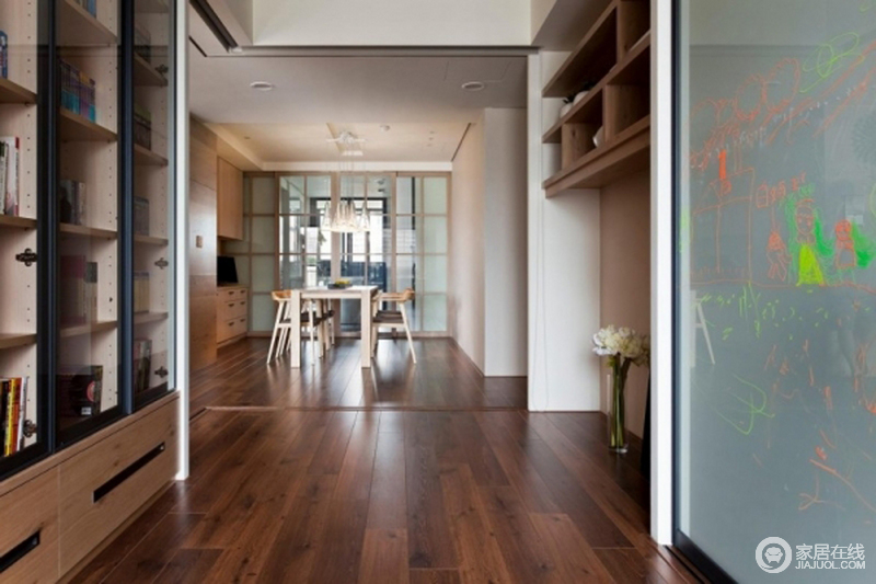 开放式的空间并没有把空间作单一化设计,而是在餐厅之外的空间,做成了一个收纳空间,同时,增加了玻璃墙,满足孩子的涂画需求;整体空间以木材为主,自然地营造出朴实感。