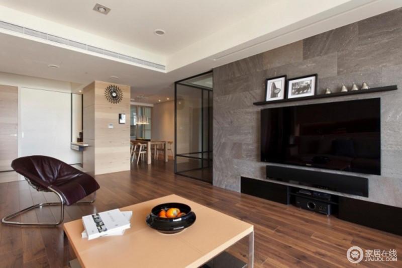 客厅的背景墙以灰色砖石铺贴出高冷与利落,线条凝练地设计,通过悬挂架和嵌入式设计,与电视构成美观与实用,平衡出简约与大气。