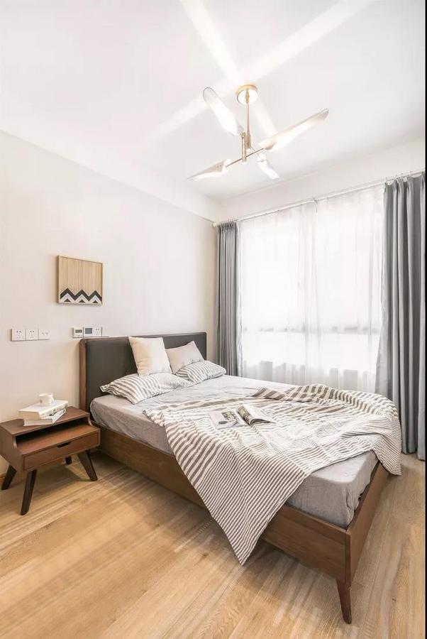 小巧的次卧用优雅的灰色做点缀,与暖色原木形成对比。考虑到实用性,设计师选择了这种带风扇的吊灯,满足屋主的生活需求