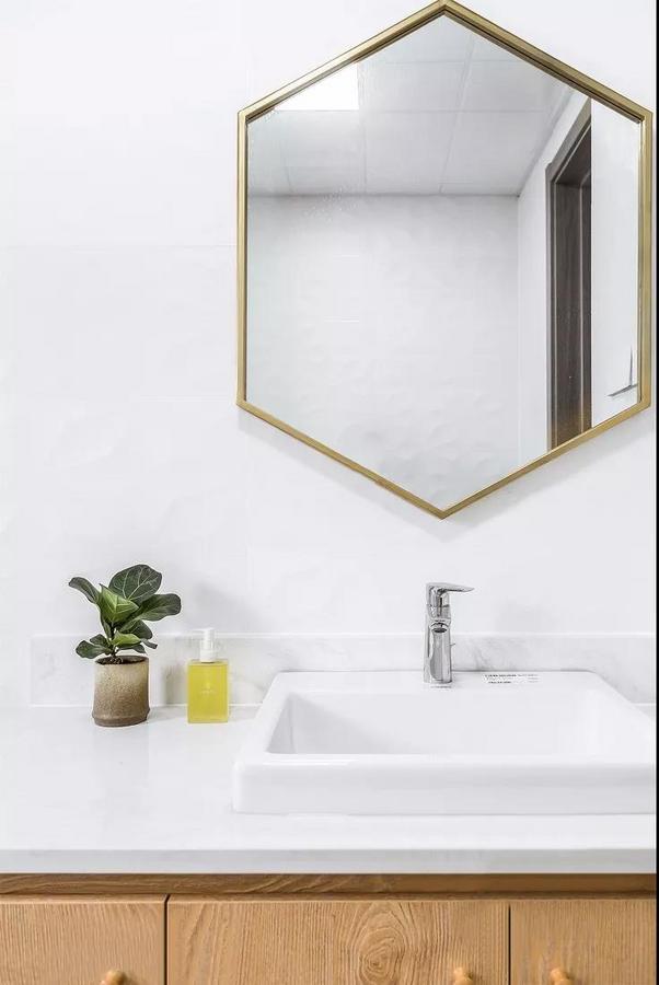 主卫,以自然系的白色 + 浅木色为主,墙面挂了一面黄铜六边镜,简约而精致。