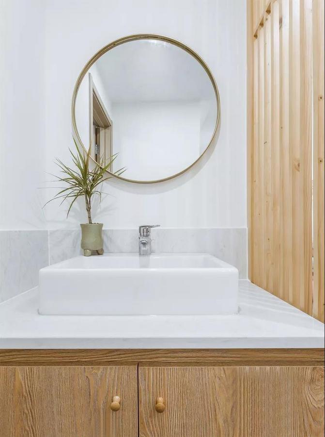 次卫,干湿分离的设计让洗手台成为另一种风格,原木风清新质朴,一面圆镜勾勒出空间格调。