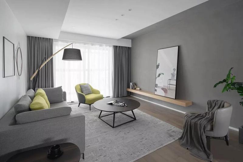 客厅以安静的灰色为主调,低饱和度的灰色调给人一种朦胧感。没有用生硬的电视柜,而是选用较为自然的装饰层板来转换色调与材质。