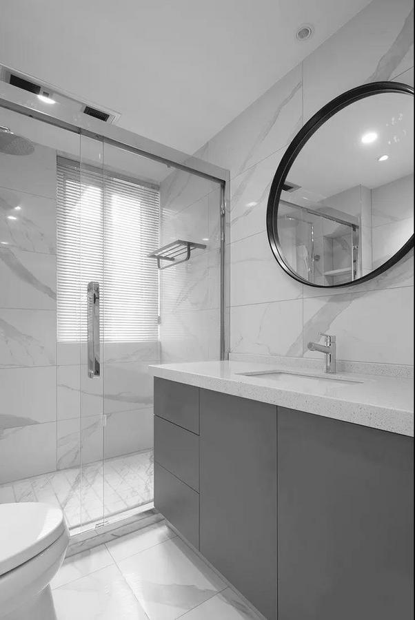 卫生间采用玻璃隔断作为干湿分区,大理石纹路的墙地砖清冷而纯净,结合黑框圆镜与灰色的浴室柜,打造出简约时尚的格调。