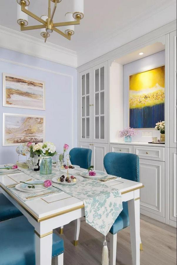 餐厅以蓝白色调为主,淡紫色和黄色为辅,结合精致的美式软装,呈现优雅而又轻奢的氛围。白色定制餐边柜美观与实用兼备,全铜拉手与金属质感的吊灯,增添了几分华丽的气息。