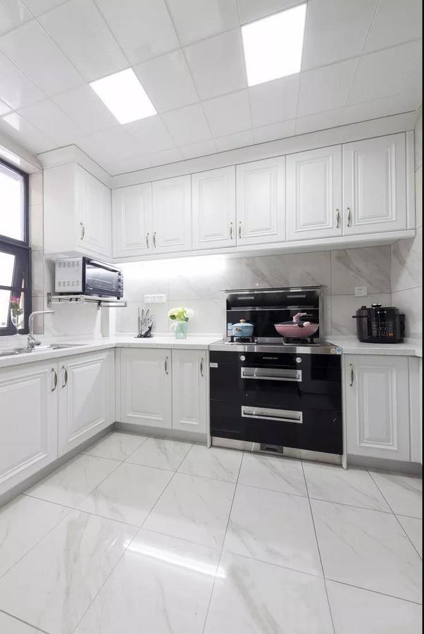 厨房白色的橱柜配以金色拉手,带来一种优雅洁净感。粉、蓝色调的加入,为主人的生活增添了一抹从容。