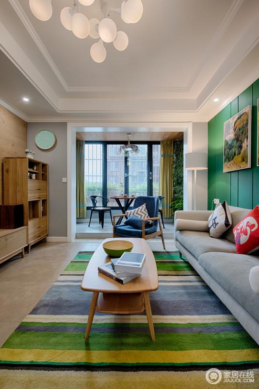 从客厅便可看到阳台处的落地窗给空间带来充足地采光,黄绿色窗帘与阳台混杂着进入室内,带来一种自然的清气;而绿色条纹地毯环境了灰色布艺沙发的沉闷,与实木茶几、实木单椅组成自然之趣。