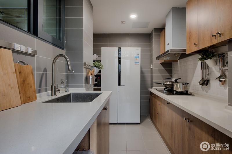 厨房线条简单,浅灰色墙面与米色地砖让整个空间的氛围格外柔和;米白色台面与实木橱柜温实的质地和自然的色调,构成简约和轻和,让生活毫无压抑感。