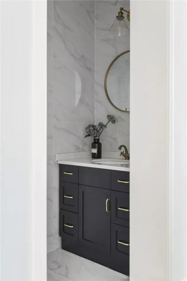 卫生间选用大理石瓷砖搭配黑色浴室柜,深色系便于清洁,抽屉式收纳柜利于分类使用,使空间更加干净整洁。