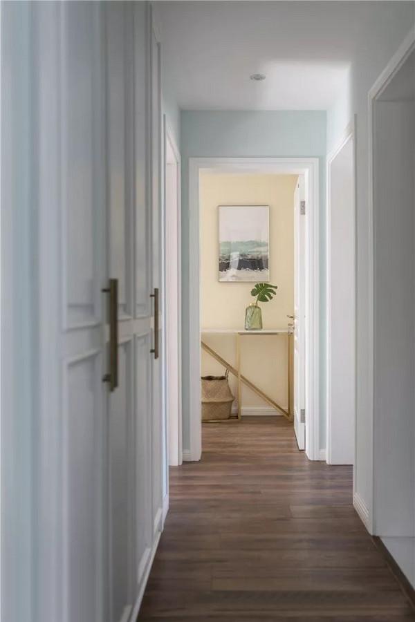 走廊量身定做了柜子,隐藏着巨大的收纳空间,嵌入式的设计以及白色的柜门保持走廊整洁的观感。