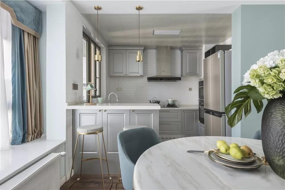 餐厅正对厨房,厨房做成开放式设计,增添了明亮的光线。同时在左侧增设吧台,不仅提供了更多的食材操作空间,也增加了家人之间的情感交流。