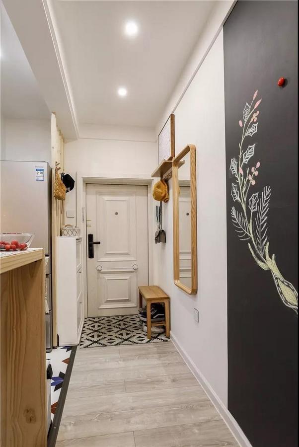 入户处做了简单的玄关设计,换鞋凳、鞋柜一样也不能少,墙面上方的隔板和挂钩让回家后的外套和包包都有了去处。