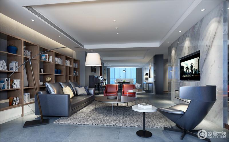 开放式的设计让人无拘无束,原木书柜简约而实用,并与平整的灰白色大理石背景墙承载着材质的魅力;北欧落地灯纤细的灯杆成为焦点,与黑灰色皮质沙发、红色沙发以色彩对比绽放着现代时尚。