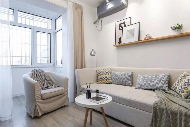 客厅以浅色调为主,沙发背景墙上设置了隔板,几何挂画和绿色小植物为空间增色不少。米色布艺沙发造型简约,柔软温暖,配以黄色+灰色的几何抱枕及格调小物为点缀,整体清爽洁净。