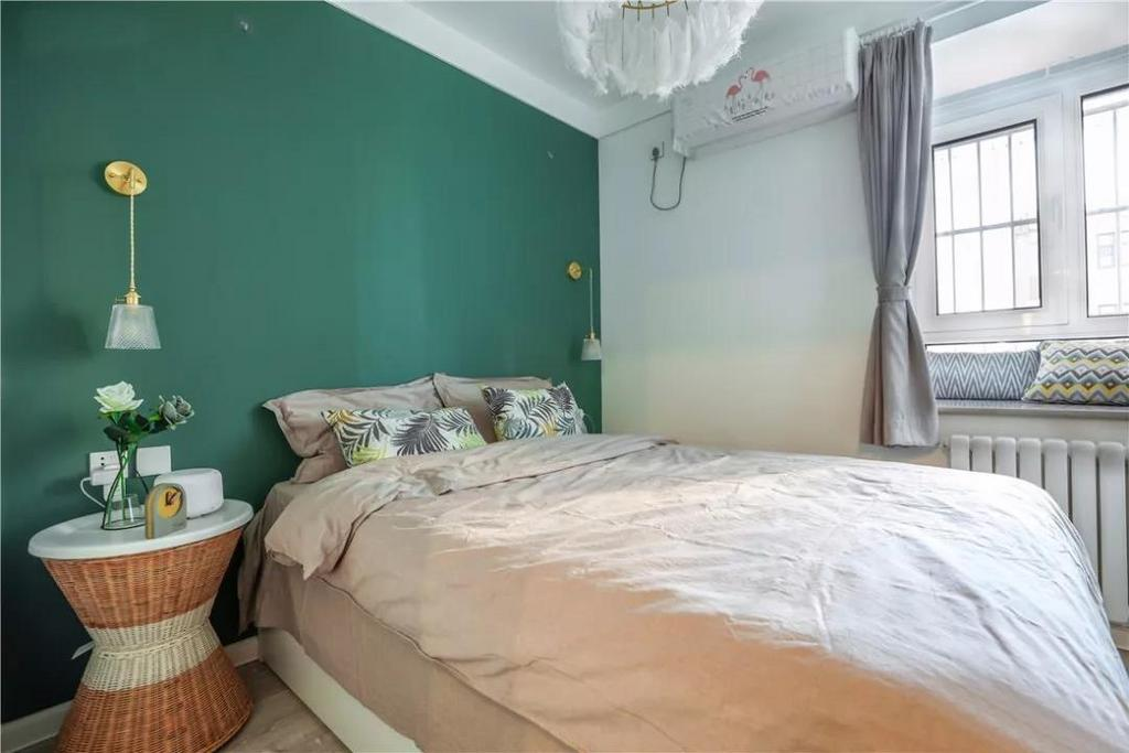 卧室主打的也是舒适自然风,绿色背景墙给人清新养眼之感。