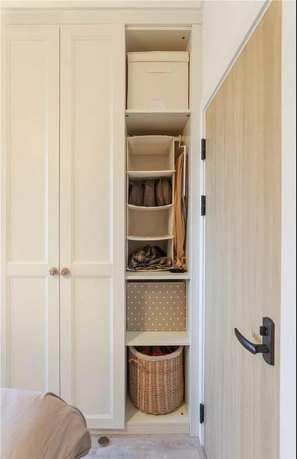 顶天立地的衣柜设计,充分满足衣物收纳需求。衣柜内部设置了各种类型的收纳筐,区分衣物,整洁有序。