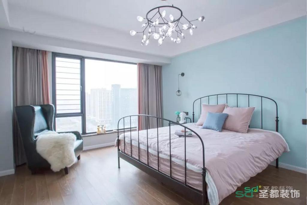 次卧的装修和主卧比较相似,浅蓝色的背景墙,一个大大的落地窗。