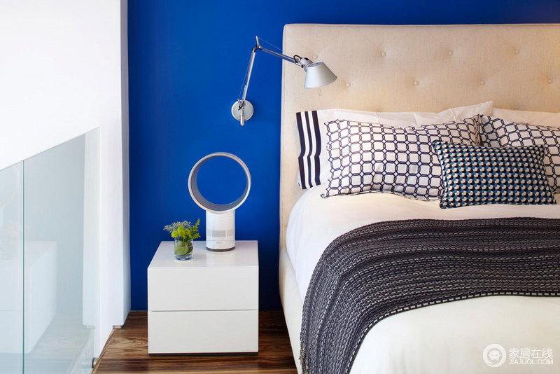 蓝色的床后的墙上,简约的床头装饰。