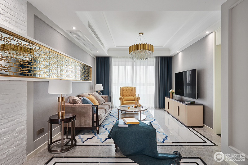 客厅以浅色作为背景色,姜黄色的沙发以及抱枕作为点缀,让整个客厅空间中咖色法兰绒沙发更显轻贵;深蓝色的抱枕、与菱形地毯作为辅色,让色彩更加丰富,沙发背景墙局部以金属镂空装饰衬托黄铜水晶吊灯,并与茶几上金色小摆件与之相互呼应,构成现代美式的华贵。
