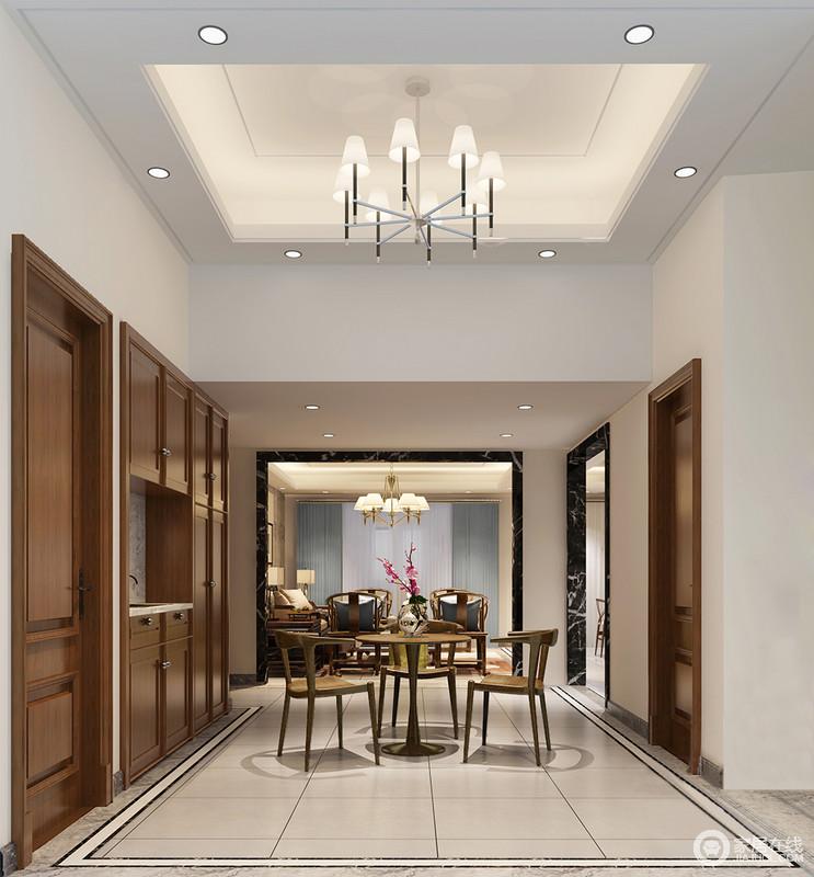 餐厅因为挑高而显得空阔,灯带、射灯与吊灯让整个天花都格外通明,让原本米色与棕黄色实木营造的空间氛围更为温馨;定制得收纳柜增强了空间的实用,而新中式圆桌与木椅的轻简大气,无形中演绎出新式东方的别致。